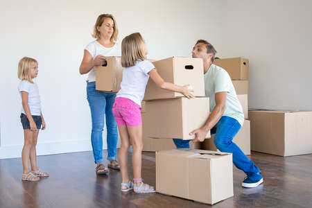 Young family carrying boxes into new home or apartment. Cute daughter helping father with belongings. Blonde mother in jeans standing and holding box. Mortgage, relocation and moving day concept