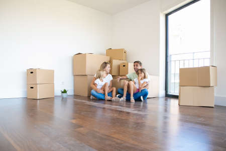 Happy young family relaxing on floor during relocation and talking. Parents holding daughters. Exited middle-aged father telling story to girls and wife. Mortgage, relocation and moving day concept Imagens