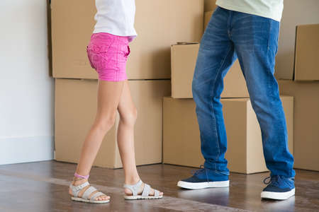 Closeup leg s of father and daughter standing among carton boxes in new home. Unrecognizable man in jeans and girl in shirts running into new apartment. Family, relocation and moving day concept 写真素材