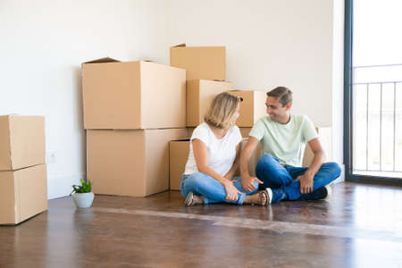 Happy wife and husband sitting cross-legged on floor in new apartment near cardboard boxes. Caucasian couple relaxing during relocation and looking at each other. Mortgage and family concept Фото со стока