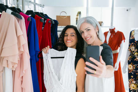 Cheerful cute female friends enjoying shopping in boutique together, holding dress, having fun and taking selfie on mobile phone. Consumerism or shopping concept 版權商用圖片