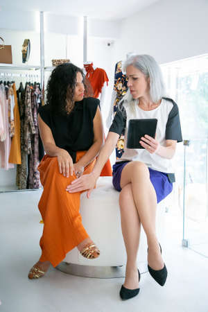 Two women sitting together and using tablet, discussing clothes and purchases in fashion store. Front view. Consumerism or shopping concept
