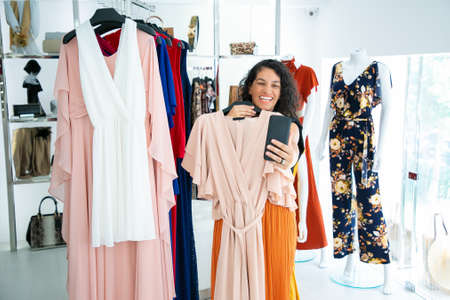 Joyful woman shopping in clothes store and consulting friend on cellphone, showing dress on hanger at frontal camera. Boutique customer or communication concept 版權商用圖片