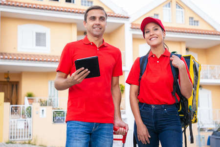 Cheerful post workers standing, smiling and working together. Happy couriers delivering order in thermal bag and wearing red shirts. Man holding tablet. Delivery service and online shopping concept Archivio Fotografico