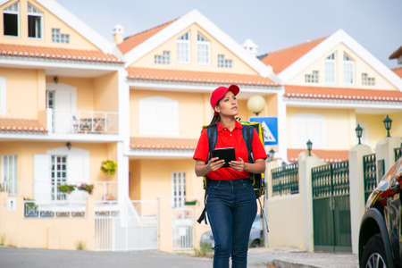 Latin deliverywoman looking for address and holding tablet. Young female courier delivering order in yellow thermo backpack. Houses on background. Delivery service and online shopping concept Archivio Fotografico
