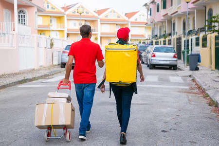 Back view of two couriers walking with boxes on trolley. Delivery people delivering order in thermal backpack and wearing red shirt or cap. Delivery service and online shopping concept