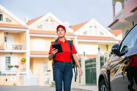 Latin female courier going and holding tablet with address. Focused deliverywoman delivering express order in yellow thermal backpack. Houses on background. Delivery service and post concept Archivio Fotografico