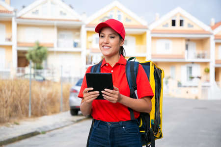 Happy female courier delivering order and working in post service. Smiling deliverywoman in red cap and shirt carrying yellow backpack and holding tablet. Delivery service and online shopping concept