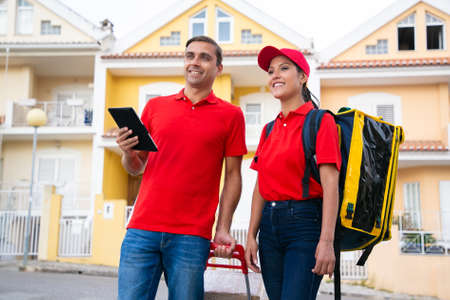 Smiling post workers standing and looking for house address on tablet. Two happy couriers delivering order in thermal bag and wearing red shirts. Delivery service and online shopping concept