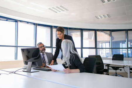 Company managers reporting to female boss. Businesspeople sitting at meeting table with holding paper and talking. Business discussion or teamwork concept