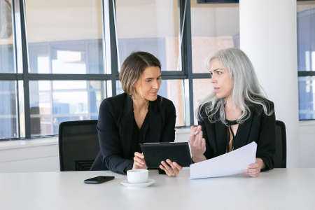 Project managers analyzing reports. Two female business colleagues sitting together, looking at documents, using tablet and talking. Front view. Communication concept