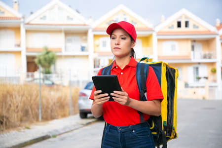 Confident female courier delivering order and holding tablet. Deliverywoman wearing jeans, red cap and shirt and carrying yellow thermal backpack. Food delivery service and online shopping concept Archivio Fotografico