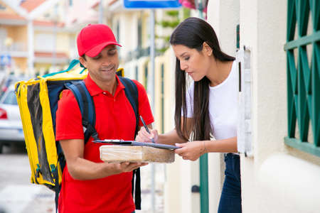 Pretty long-haired woman receiving package from deliveryman. Middle-aged courier standing, smiling and holding clipboard on parcel when customer signing receipt. Delivery service and post concept