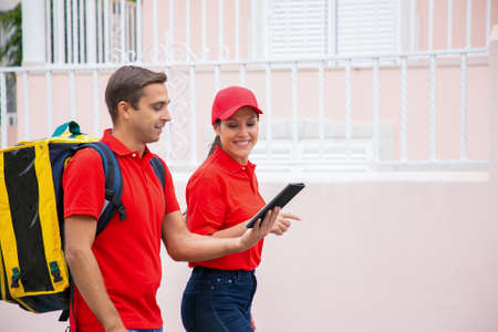 Side view of couriers delivering order and holding tablet. Man and woman wearing jeans and red shirts. Deliveryman carrying thermal backpack. Food delivery service and online shopping concept Archivio Fotografico