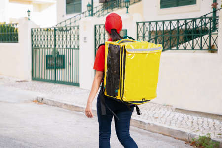 Back view of deliverywoman carrying yellow thermo bag. Experienced courier walking on street outdoors and delivering order. Fence on background. Food delivery service and online shopping concept