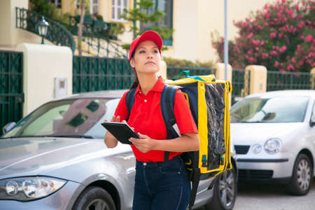 Young female courier looking for house and holding tablet. Pensive deliverywoman wearing red cap and shirt and carrying yellow thermo bag with order. Delivery service and online shopping concept