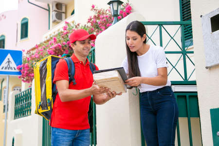 Happy deliveryman holding clipboard when customer signing. Pretty long-haired woman receiving package. Smiling courier carrying thermo backpack and delivering order. Delivery service and post concept Archivio Fotografico