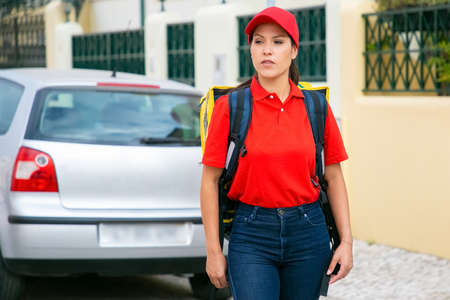 Content deliverywoman carrying yellow thermal bag. Young courier in red shirt looking for address and delivering order. Car out-of-focus on background. Delivery service and online shopping concept