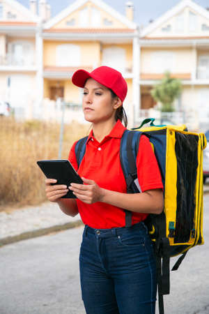 Concentrated female courier delivering order and standing on street with tablet. Professional deliverywoman with yellow backpack looking for address. Delivery service and online shopping concept