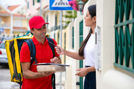 Woman holding pen for signing receipt of delivered package. Caucasian handsome courier in red uniform standing outdoors with parcel and delivering order to customer. Delivery service and post concept