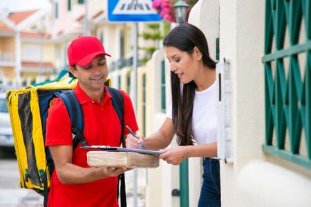 Beautiful young woman putting signature in clipboard for getting package. Smiling Caucasian deliveryman in red uniform holding cardboard box and carrying thermal bag. Delivery service and post concept