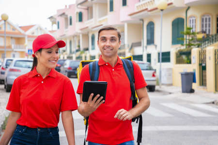 Cheerful post office workers looking for address on tablet. Man carrying yellow thermal bag. Couriers in red shirts walking on street and delivering order. Delivery service and online shopping concept