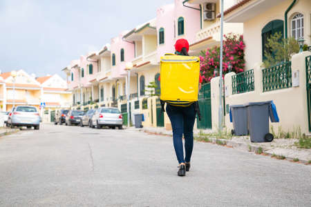 Back view of deliverywoman carrying yellow thermal bag. Female courier in red cap walking along street and delivering order. Houses on background. Food delivery service and online shopping concept