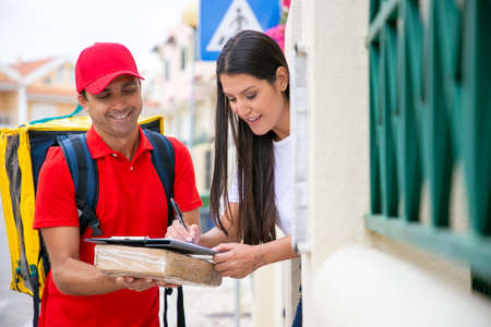 Smiling woman receiving parcel box from deliveryman. Postman holding cardboard box and beautiful female customer putting signature in clipboard to confirm receiving. Delivery service and post concept