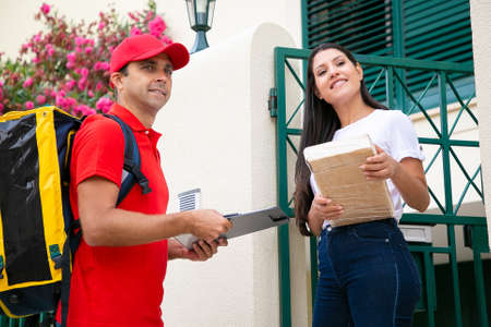 Caucasian deliveryman wearing red uniform holding clipboard in front of house. Beautiful brunette woman accepting parcel or box from postman and smiling. Home delivery service and post concept