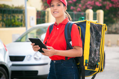 Cropped female courier looking at camera and holding tablet. Professional deliverywoman in red cap and shirt carrying yellow thermo bag and smiling. Delivery service and online shopping concept