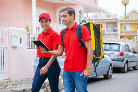 Happy couriers delivering order, working in express service and wearing red cap and shirt. Deliveryman carrying yellow backpack and holding tablet. Delivery service and online shopping concept Archivio Fotografico