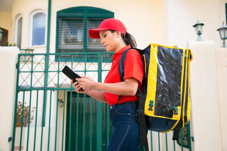 Serious female courier watching address on tablet and carrying yellow thermo bag Deliverywoman in red cap delivering express order on foot. Food delivery service and online shopping concept Archivio Fotografico