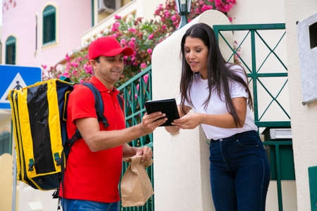 Happy courier holding clipboard and woman signing. Positive deliveryman in red cap and shirt carrying, thermo bag and delivering express order to female customer. Delivery service and post concept Archivio Fotografico