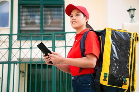 Smiling female courier with yellow thermal bag delivering order on foot. Cheerful deliverywoman in red cap and shirt walking on street with tablet. Delivery service and online shopping concept