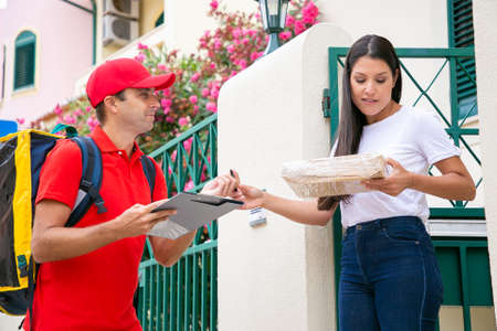 Pretty woman getting parcel from deliveryman in red uniform. Happy Caucasian courier carrying yellow thermal backpack, smiling and delivering order to customer. Delivery service and post concept Archivio Fotografico