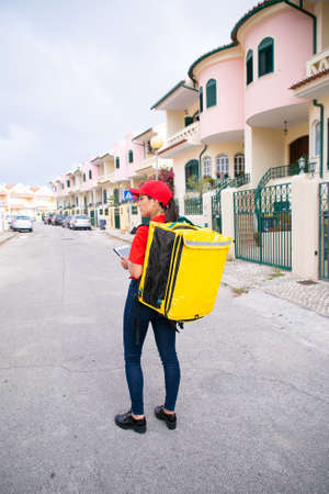 Female post worker in red cap standing with yellow thermal bag and holding tablet. Deliverywoman delivering order on foot. Houses on background. Food delivery service and online shopping concept
