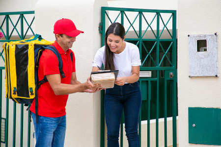 Cheerful brunette woman signing in delivery sheet with pen. Smiling postman with thermo backpack holding clipboard on parcel, standing and wearing red uniform. Delivery service and post concept Archivio Fotografico