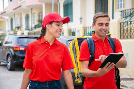 Happy man in red cap showing address to colleague. Smiling couriers working together and delivering orders on foot. Houses and cars on background. Delivery service and online shopping concept Archivio Fotografico