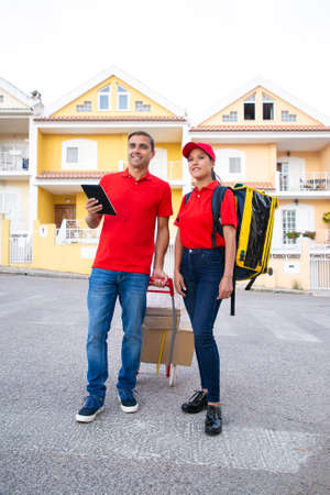 Happy couriers standing and watching address via tablet. Cheerful post workers delivering order together in thermo backpack and cardboard boxes on trolley. Delivery service and online shopping concept
