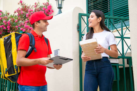 Cheerful woman receiving parcel from courier and smiling. Happy deliveryman with yellow thermal backpack wearing red uniform and talking with female customer. Home delivery service and post concept