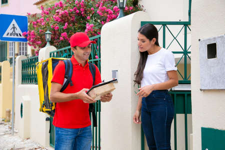 Professional postman reading order data to customer. Woman standing outdoors and listening man. Courier with thermal bag holding clipboard and parcel or package. Delivery service and post concept