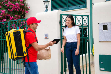 Caucasian courier delivering order to customer and showing data on clipboard. Professional deliveryman carrying yellow backpack and packet. Woman watching on paper. Delivery service and post concept