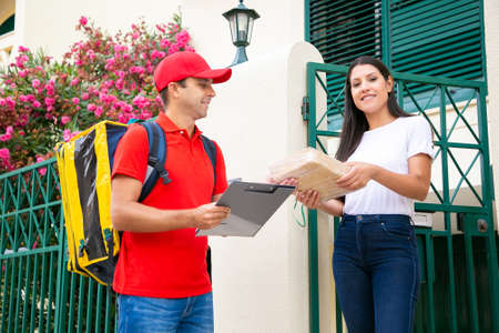 Brunette woman accepting package from professional deliveryman and looking at camera. Happy postman delivering order to customer, standing outdoors and smiling. Home delivery service and post concept Archivio Fotografico