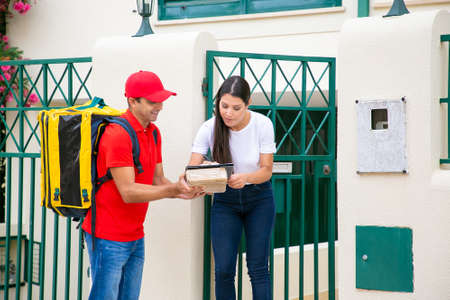 Long-haired female client signing in delivery sheet with pen. Smiling deliveryman with thermal bag holding clipboard on parcel, standing and wearing red uniform. Delivery service and post concept