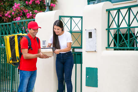 Happy female customer signing in delivery sheet with pen. Smiling courier with yellow backpack holding parcel and clipboard, standing and wearing red uniform. Delivery service and post concept