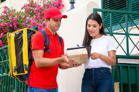 Pretty woman putting signature in clipboard and courier holding box. Brunette female customer accepting delivery of parcel from deliveryman in red uniform. Home delivery service and post concept Archivio Fotografico