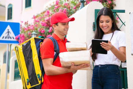 Happy deliveryman standing near customer with tablet. Professional postman in red uniform holding boxes and delivering order. Pretty female client getting parcels. Delivery service and post concept