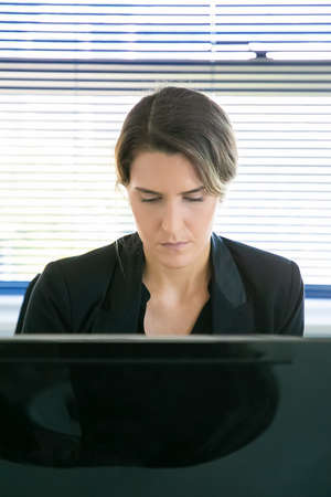 Content female CEO sitting and working via computer. Successful pensive beautiful businesswoman doing her job, thinking and looking down on monitor. Business, expression and workflow concept