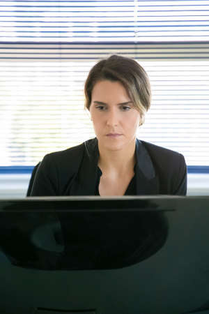 Experienced businesswoman sitting in office room and looking at screen. Caucasian content pretty office employee working on project via computer. Business, digital technology and corporation concept