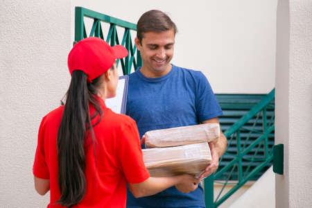 Smiling male customer receiving parcels. Long-haired deliverywoman giving cardboard boxes to happy customer. Female courier in red shirt delivering order and talking. Delivery service and post concept